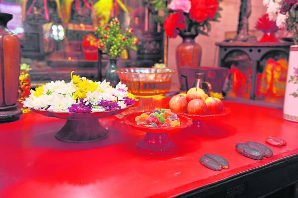神案上不同颜色的菊花有不同功效: 白花赐子、红花赐女, 黄花则是保佑平安。