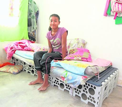 灾民开心的搬运慈济福慧床,因为家园尽毀的他们,可以不用再躺在地上受苦。
