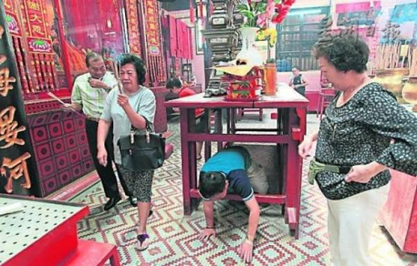 """仙四师爷庙每逢除夕至开年期间,有一项""""钻神桌底求平安""""的习俗,不少善信慕名前来,不分老少,诚心膜拜后就开始低头钻过神桌底。"""