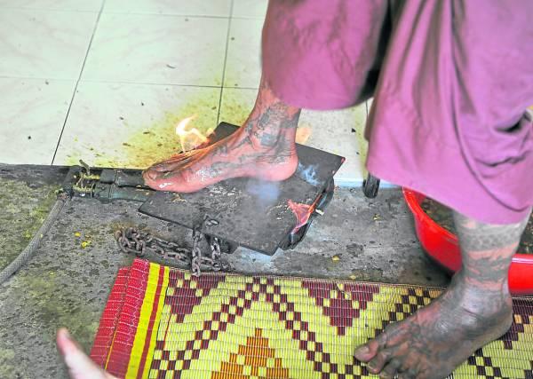 泰国高僧Prapot赤脚踩踏在被烧得火红的铁板上,面不改色毫无损伤,再轻轻地在病患身上踩几下、踏几下,据说有驱病解降的神奇效果。