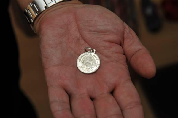 金口师父手上拿的就是孔雀神神牌,神牌戴在身上可以保佑平安。