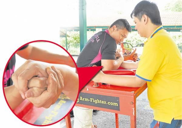 萧汉铭与记者一起示范腕力摔角动作,他强调除了握紧对方的手,肚子更要贴着桌子(擂台),力气才能瞬间爆发击倒对手。