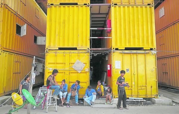 放工了,工人们坐在货柜家外面聊天,一天又一天,期盼赚了钱,回家的那一天。