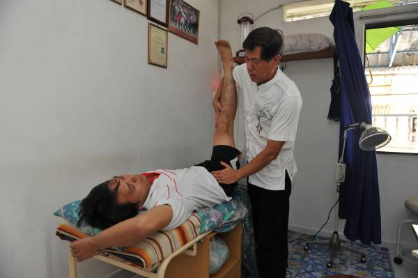 郭医师把病患的脚抬至30度,就可以检验出脊椎移位的问题。