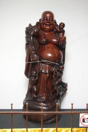 """一尊千年红豆杉笑佛是""""新加坡古佛佛行""""的镇馆双宝之一,曾有人以100万人民币高价求购,但被洪镇鹏一口拒绝了。"""