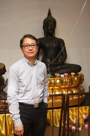 """洪镇鹏是""""新加坡古佛佛行""""的创办人 ,其身后的古佛便有八百年历史,据说市值两百万美元。"""