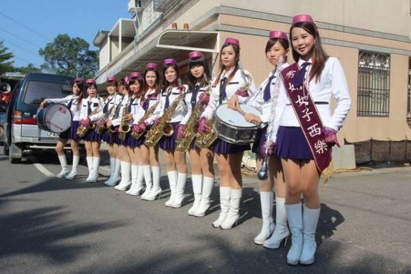 秀娟乐团成员都穿着超短裙,高跟鞋,上身穿着一件白衣衫,衬托出美腿翘臀。