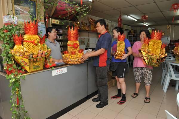 有许多慕名而来的顾客到高燕萍店里购买旺气十足的金凤梨。