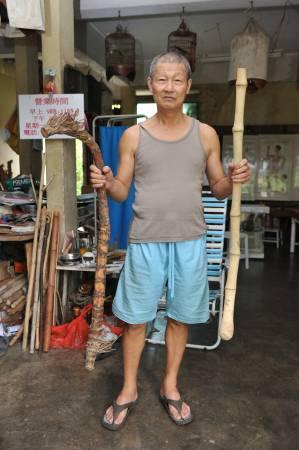 """詹达明拿出其""""珍藏""""让笔者欣赏,右边即是长得很像龙头拐杖的倒生藤和实心竹(左边)。"""