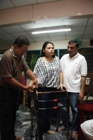 经过王医师治疗后,中风病患Saidina能撑着助行器慢慢站起来。
