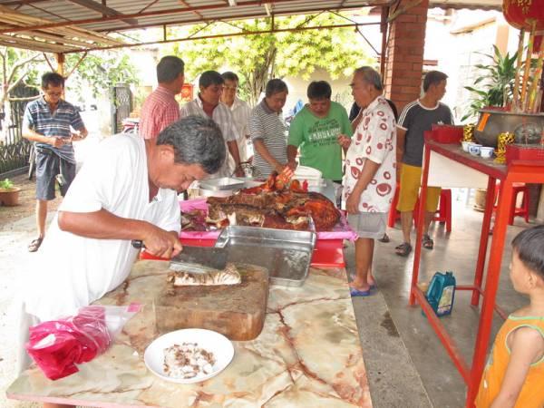 信徒中万字买金猪来答谢神恩,在场善信吃烧猪肉沾财气。