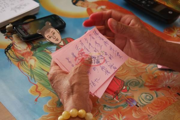 """杨九妹将还债人的姓名、时辰八字等写在一张粉红色的字条上,作为禀告千手观音的""""信"""",并于还债仪式时将字条和福星一起化掉。"""