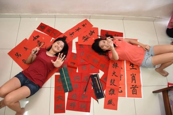 双胞姐妹雯倪(左)及雯迪自幼学书法,每逢新年更是亲自挥毫春联送给亲友,如同把双倍的祝福赠送给亲友。