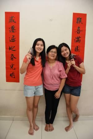 雯倪(姐姐,右)及雯迪自幼学书法,更获奖无数,亲友收到她们亲自挥毫的春联,都会高兴得贴墙增添春节气氛。