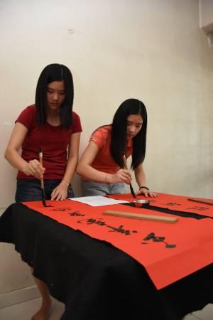 现场两人轻松在红纸上挥毫,对联涵义吉利。