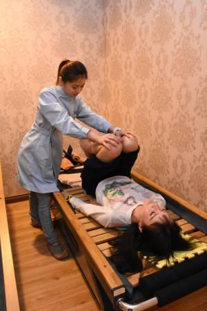 护理人员小心翼翼地为Carolyn进行脊椎疗理。