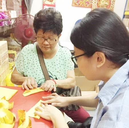 茹女士正细心的教导如何折各种金纸。
