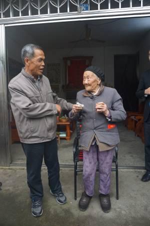 江十一嫂是长寿村里最年长的一位,如今104岁的她已四代同堂,但仍可以到邻居家串门子,左为其幼子江富山。