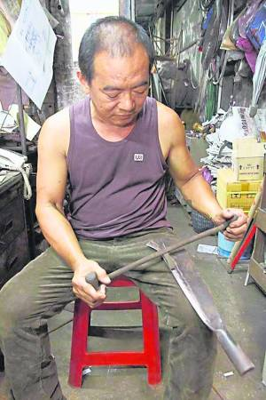 游陆辉展示及讲解操作古老手工磨铁工具。