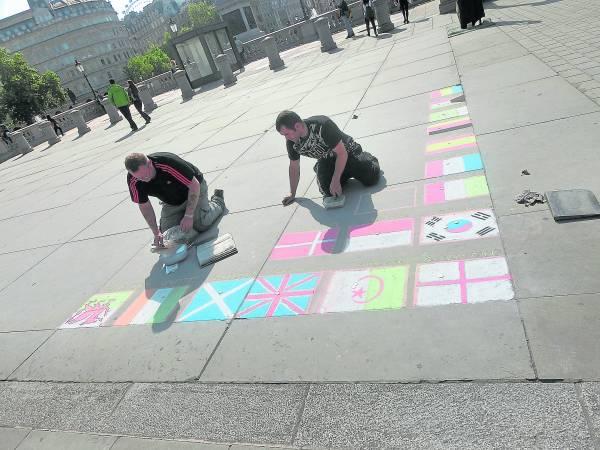 街头艺术家就地施展才艺,吸引旁人围观。