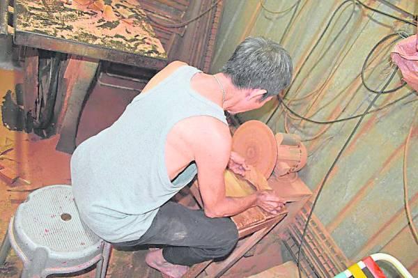 1.陈德龙用机械把木头锯开,再削刨成木屐雏形。