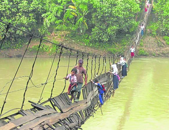 勇敢的孩子们,抓着烂桥的钢索,小心的越到对岸,只为了完成一条上学路。