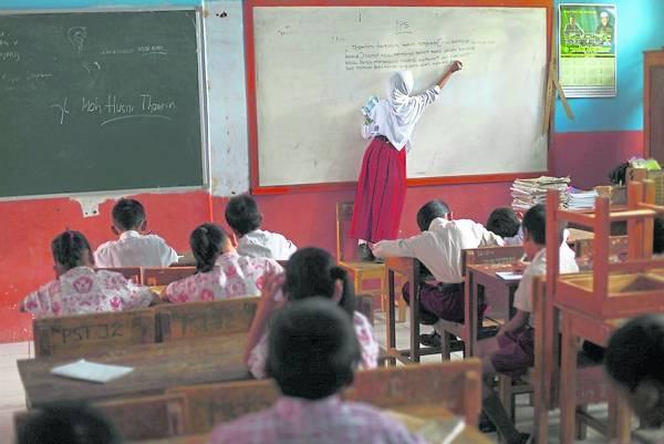 在课室里,索菲亚指导其他同学。她是那么地乖巧和坚强。