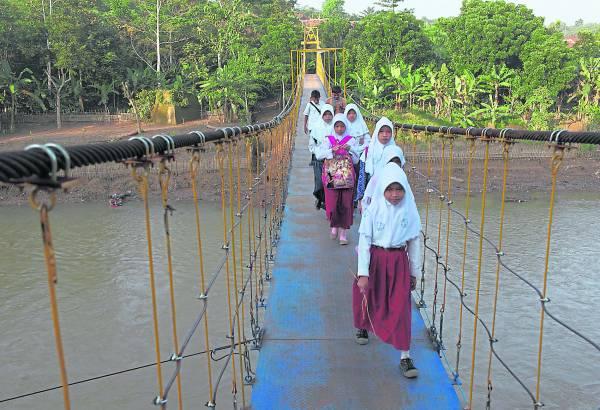 """烂桥事件的10个月后,印尼最大的钢铁厂PT Krakatau Steel (KRAS) 和非政府组织建了一条新的吊桥。孩子们结束300多天的""""艰辛上学路""""。"""