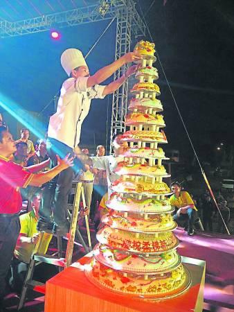 配合柔州优景镇庙庆十四周年,赞助商特别要求订制十四层蛋糕。在叠蛋糕的过程中险象环生,最终顺利完成,全场逾千人欢呼声不断。