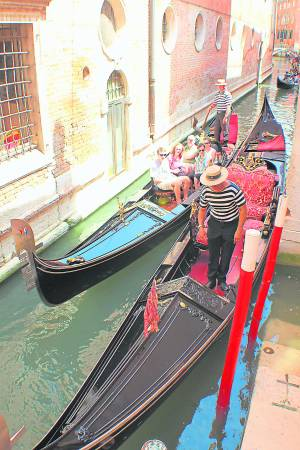 古典梦幻浪漫船只贡多拉(Gondola),以及穿着条纹T恤,撑着船杆的帅气船夫。