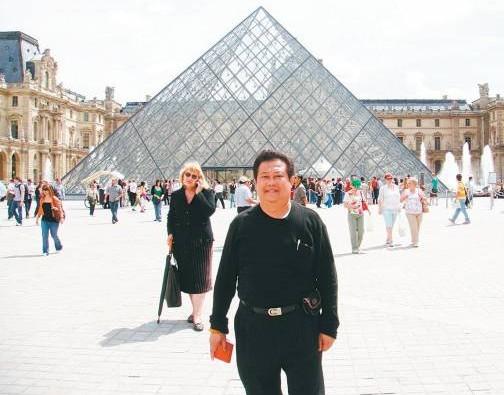"""谭师父站在罗浮宫前面的""""玻璃金字塔"""",中国建筑师贝聿铭所设计的,其设计据说借鉴了中国的风水之说。"""