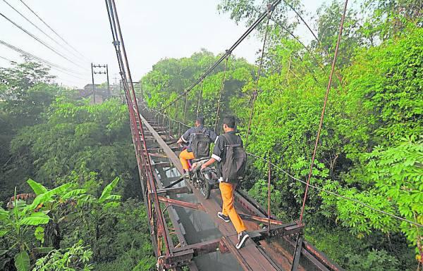 这座旧桥距离下面的河面有30多米高,如果上面有人滑落下去,将必死无疑,但仍有人甚至骑着摩哆车从狭窄的吊桥上通过。