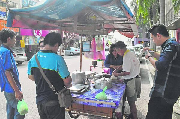 老街坊喜欢围在三轮车旁,一边享用美味麦粥,一边话家常。