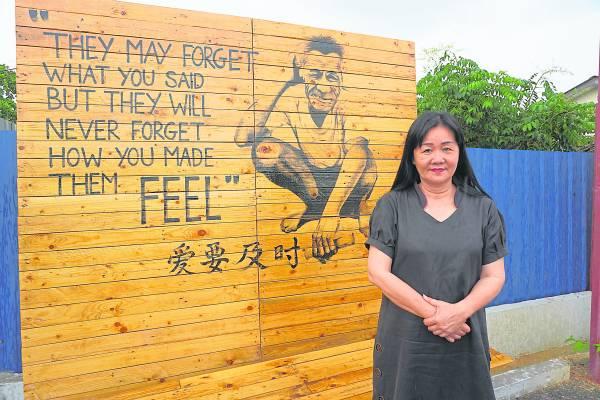 叶丽娟女士与the one academy学院为佳宁乐龄之家所绘制的图合照。