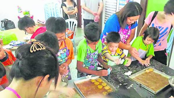 中秋节将至,热心义工来教小朋友做月饼。