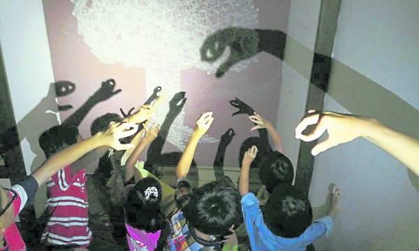 义工来探望小朋友,偶尔也会教他们玩影子游戏。
