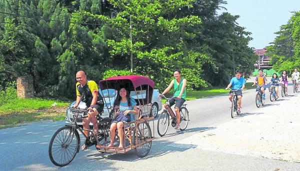 游客骑着踏脚车到邻近的甲板古镇游览。