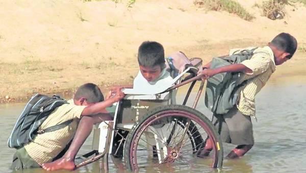 阿山坐在轮椅上,依赖两位年幼弟弟辛苦推轮椅,一路护送上学。