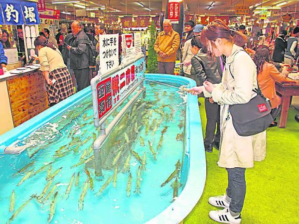 """日本函馆传统朝市可以让食客现钓墨鱼,在另一边还有厨师即场为你用墨鱼做料理,几乎每位食客吃后都高呼""""好吃""""!"""