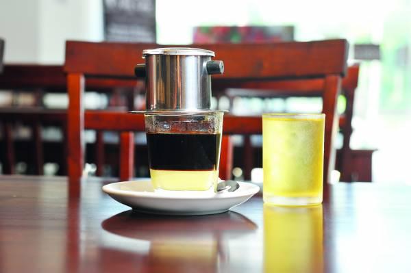 越式咖啡+奶,店家贴心地附上一杯清茶,让食客在等待咖啡滤.