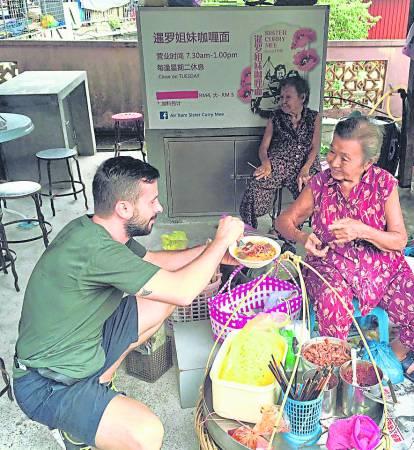"""老外对""""槟城金银婆婆""""煮食的咖哩面赞不绝口,甚至不介意蹲着吃起来。"""