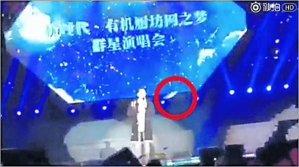 王力宏在台上被丢水瓶,直中腹部,让他痛得缩起身子来。