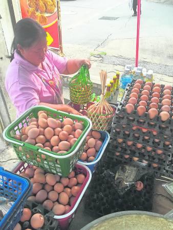 佛寺外除了有许多摆卖熟鸡蛋的小档口外,还有许多卖大彩的小摊子!
