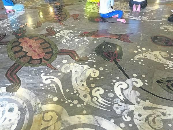 主殿内地面全是云石图画,画中各种类形的鱼、蝦、螃蟹、青蛙等都从四面八方游来迎金佛供奉。