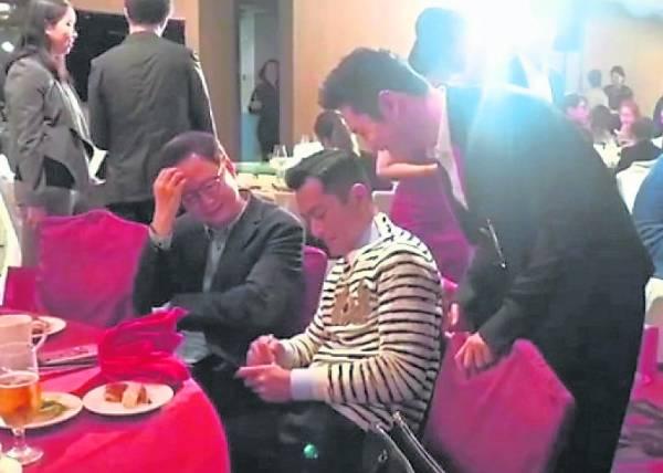 黄晓明在星光熠熠的活动上,如小粉丝般弯身帮员工向古天乐拿签名。