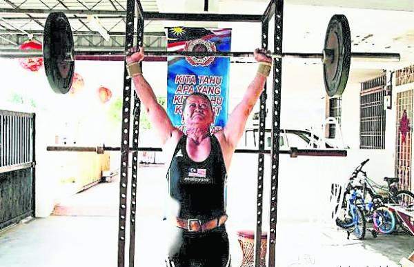 伍潮胜每周6天都会定时训练举重,60多年如一日。
