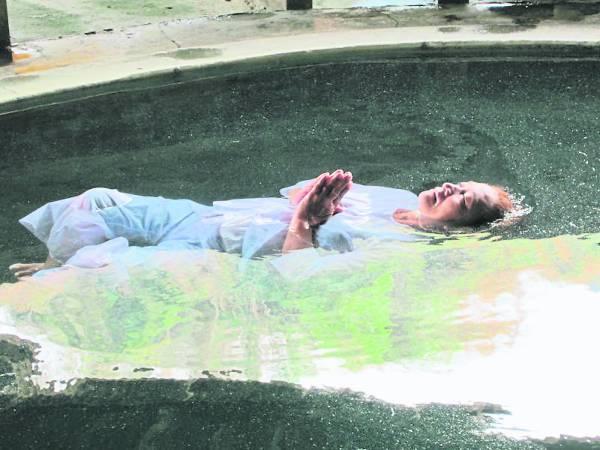 在泰国金龙洞寺,学习修行者漂浮在水池中冥想。