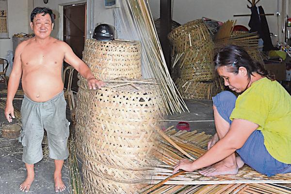 林顺和太太林亚珠以身压着已编制成形的底部,让编制的竹箩更精细美观。