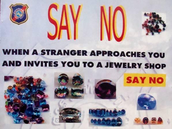 提醒游客:旅游区的告示牌,劝你勿随意相信陌生人推荐的珠宝店。