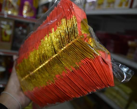 """陈智芬一天可制作逾两百个""""多用途""""的金元宝。"""